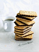 A Stack of Gluten Free Chocolate Covered Cookies; Cup of Coffee