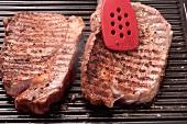 Ribeye steaks being grilled