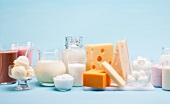 Various milk products (cheese, ice cream, milkshakes and milk) on a blue background