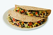 Two Vegetarian Tacos on Multi-Grain Tortillas; White Background