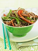 Pork and Veggie Stir Fry Over Soba Noodles in a Green Bowl with Chopsticks