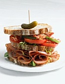 Club Sandwich with a Pickle and Toothpick; On a Plate; White Background