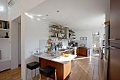 Moderne, funktionale Küche mit warmen Akzenten durch Holzfronten und Terrakottafliesen