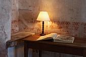 Tischlampe und aufgeschlagenes Buch auf Holztisch vor Wand mit verblasster Schablonenmalerei