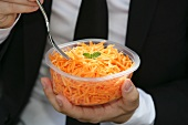 A man eating grated carrots