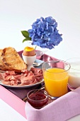 A breakfast tray with egg, toast, ham and orange juice