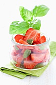 Strawberry salad with basil in glass pot on green napkin
