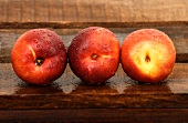 Three nectarines with droplets of water on wooden crate
