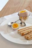 Frühstücksei, aufgeschlagen, und Toast