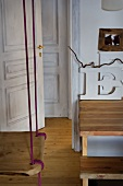 Von Decke abgehängte Schaukel und offen stehende Tür in rustikalem Ambiente