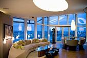 Imposanter Raum mit Wohn- und Essbereich und grosser Fensterfront in Abendbeleuchtung