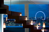 Beleuchtete Treppe vor grosser Fensterfront in Abendbeleuchtung, mit Blick auf London