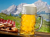 A beer and a pretzel in front of a mountain landscape
