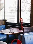 Seating in English restaurant - booths with leather benches in front of windows with line-drawing of Vespa