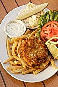 A crab cake with coleslaw, chips and a dip (USA)