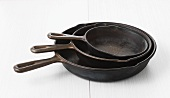 Three iron pans in different sizes