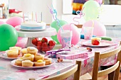 Fairy cakes, fresh strawberries and a birthday cake for children on a table with party decorations