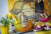 Easter decoration with bird cage, confectionary and flowers