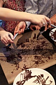 Children making chocolate decorations for cakes