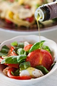 Sprinkling insalata caprese with olive oil