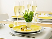 Table set for Easter with champagne flutes and eggs