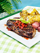 Grilled beef steak with tomato salsa and corn on the cob