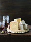 Assortment of Cheese on a Wooden Plate; Aged Goat Cheese, Gran Queso and Manchego; Figs and Red wine