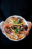 Person Holding Seafood Plate; Grilled Shrimp, Octopus and Mussels
