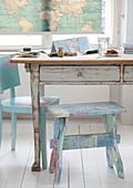 Küchentisch mit abgeblätterter Farbe und bemalter Holzschemel auf weißem Dielenboden