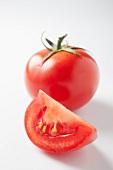 A slice of tomato and a whole tomato