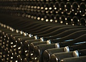 Old, dusty wine bottles with bottle tops in a wine cellar