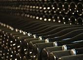 Alte, verstaubte Weinflaschen mit Kronkorken lagern im Weinkeller