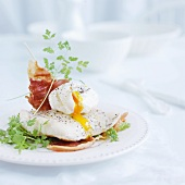 Cod fillet it with poached egg and Parma ham