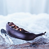 A banana baked in its skin topped with nuts and chocolate