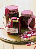 Strawberry and rhubarb jam in jars tied with ribbons