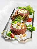 Beef tatar garnished with salad greens