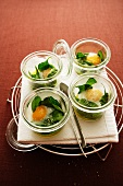 Poached quail's eggs in jars with spinach