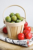 Greengages and red plums in a basket and on paper