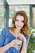 Junge Frau trinkt ein Glas Wasser mit Strohhalm