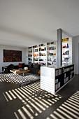 Wohnbereich im offenen Wohnraum, abgegrenzt durch ein offenes Sideboard mit Bücherregal an der Rückwand