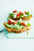 Bread topped with basil spread, tomatoes and parmesan cheese