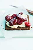 A slice pumpernickel topped with a spread and fresh cherries