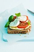 A slice of wholemeal bread topped with tomatoes, mozzarella and basil