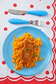 A fish-shaped fillet on a bed of grated carrots (seen from above)