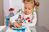 Little girl putting cress seeds on a cotton pad
