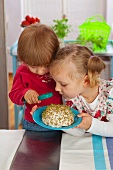 Two children watching germinating cress on a cotton pad