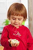Kleines Mädchen hält Brotscheibe mit Hüttenkäse in der Händ