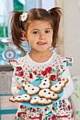 A little girl holding a plate of gingerbread snowmen