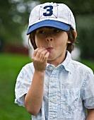 A little boy in a cap chewing