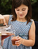 A girl pouring juice from a jug into a glass